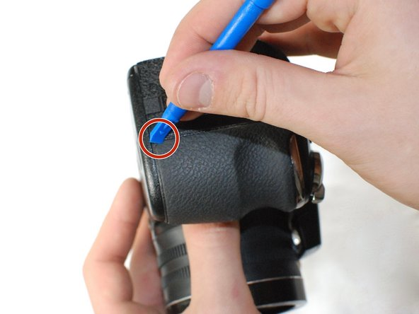 Use a plastic opening tool to pry up the corner of the grip.