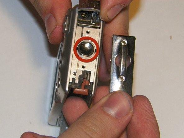 Image 2/3: Remove the small circular cover underneath the wrist strap attachment.