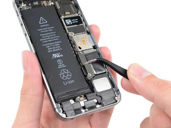 Image 1/1: Remove the metal battery connector bracket from the iPhone.