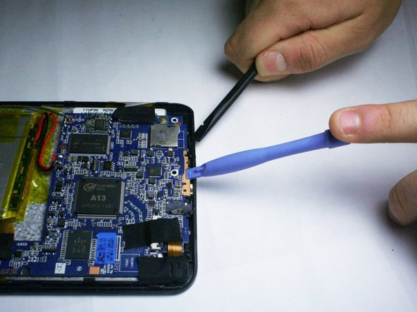 If the button did not fall out on its own, push the circuit board up with one tool while gently pushing inwards on the volume button with another tool to dislodge it.