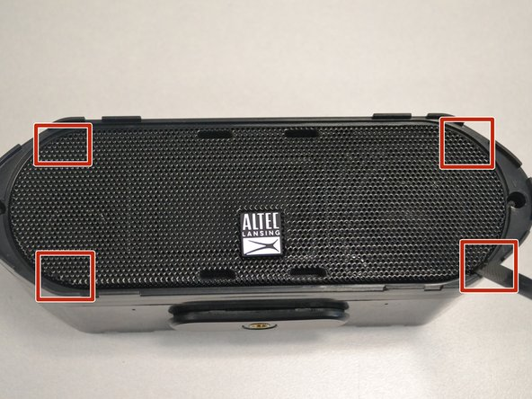 At each of the marked pry spots,  use the metal spudger to lift the speaker grill away from the case.