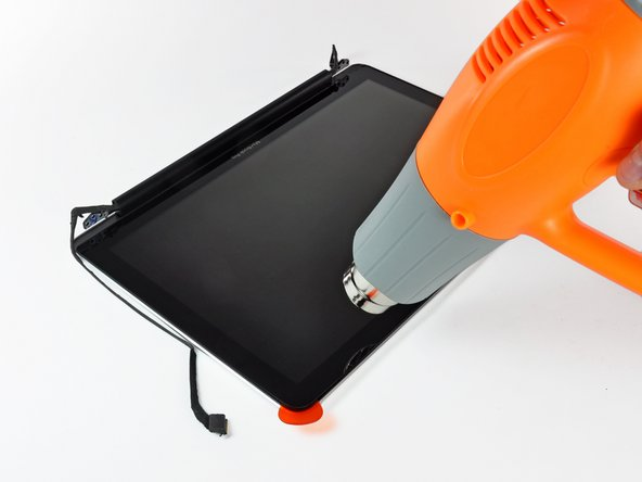 Use your heat gun to soften the adhesive under the black strip along the top edge of the glass display panel.
