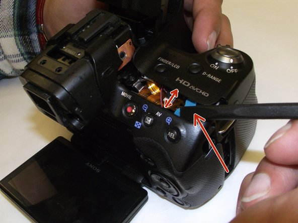 All the necessary screws are removed.  Begin prying the back away from the camera in order to remove the front cover.