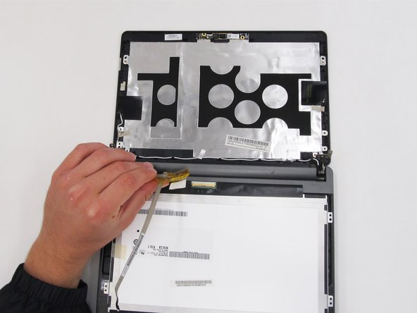 Looking at the underside of the screen, remove the yellow tape and carefully remove the wires attaching the screen to the laptop.