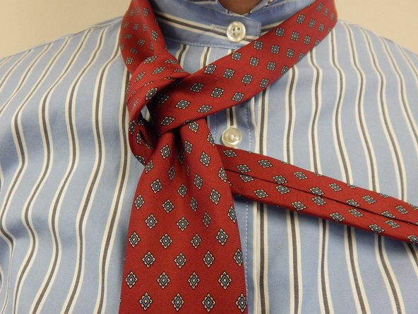 Wrap the active end under the wide end of the tie, so that it now points towards the right.