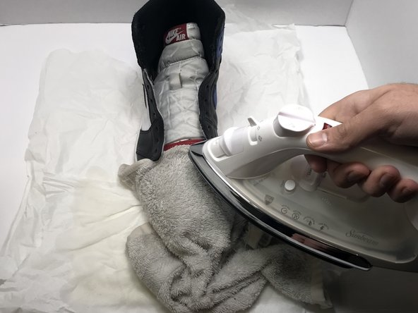 Using a flat iron, iron over the damp towel to remove toe-box creases.