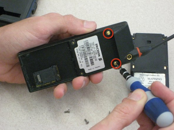 Locate the top two U-shaped screws on the back of the phone, as shown by the red circles.