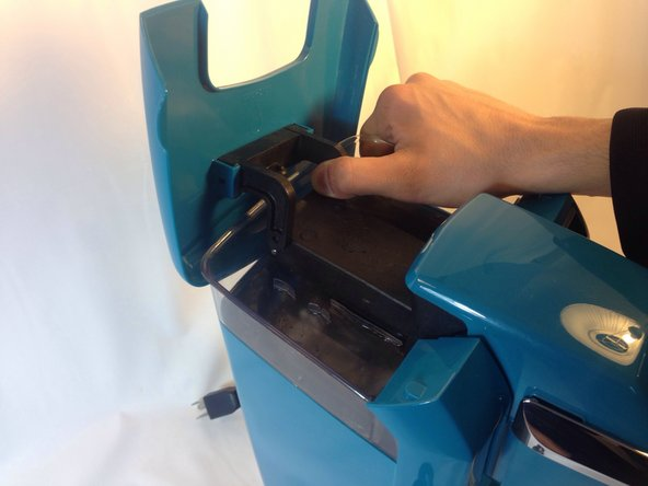 Image 3/3: Pull directly outwards on one of the arms that holds the top lid in place.  It will take some force to get the arm off the peg.  Once one side is off, repeat the process on the second arm.