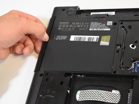Grab the optical drive by the edge and pull it out.