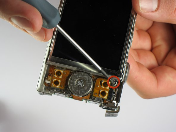 Image 2/2: Using the #00 Phillips-head screwdriver, remove the two screws located on the bottom of the camera, as well as the single screw located next to the LCD screen (refer to pictures).