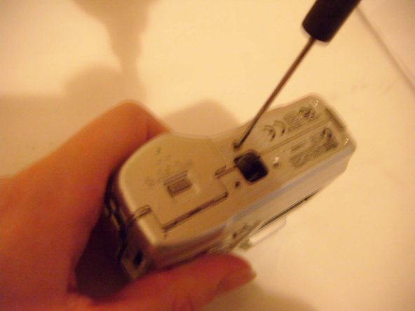 Use a small Philips screwdriver to remove the screws from the base of the camera.