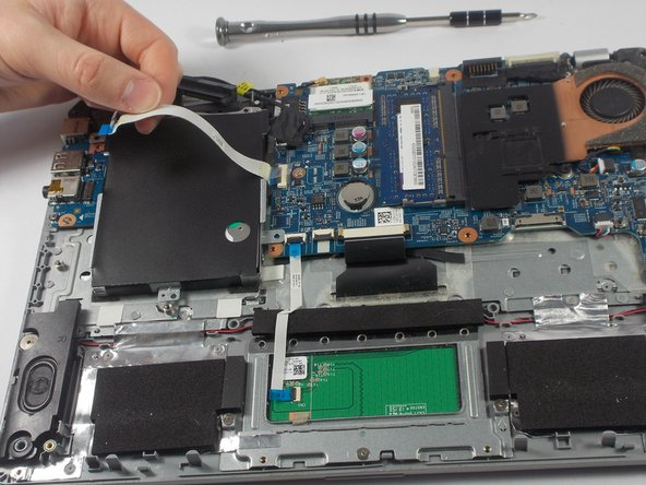 After removing the plastic piece that holds the cable in place, you can lift the ribbon cable up high enough to remove the hard drive.