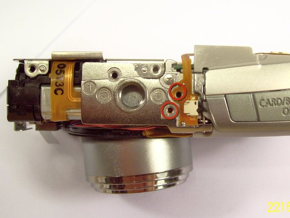 Remove the two screws near the the tri-pod mount with a Philips head screw driver.