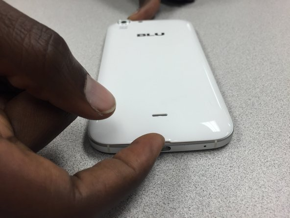 Remove the back cover by lifting at the notch towards the bottom of the phone. Use your fingernail to pry up.