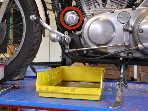 Image 1/3: Move the oil pan to the front of the bike, directly underneath the oil filter.