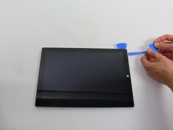 Use a plastic opening tool to separate the screen from the device.
