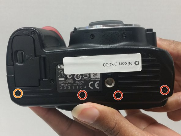 Removal of the screws from the bottom will aid in the removal of the back as it loosens the bottom tabs of the camera back.