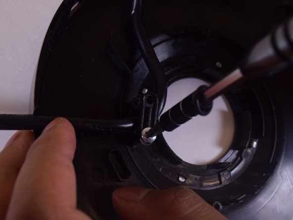 Remove the two rounded top (12mm) Phillips Head screws from the 1'' bar holding down the power cord.