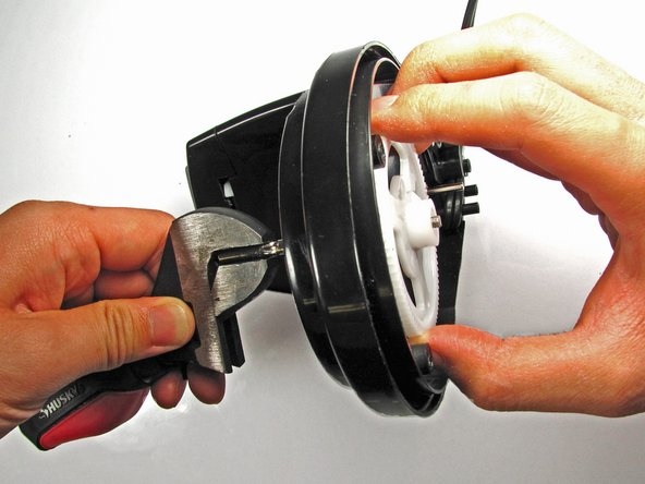 Image 1/3: Grab the gear with your other hand and turn '''''CLOCKWISE.''''' Unlike most screws, the gear is reverse-threaded to allow the blade to spin.