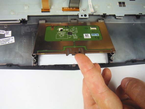 Image 2/3: Lift up and remove the touch pad from the palm rest assembly.