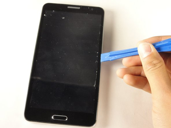 Using the plastic opening tool, create space between the front screen and the metal casing.