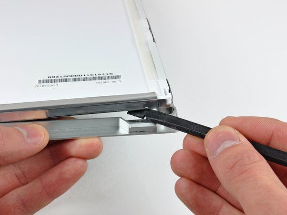 The next few steps will require you to separate the LCD from the adhesive applied to the upper and lower edges of the front bezel.