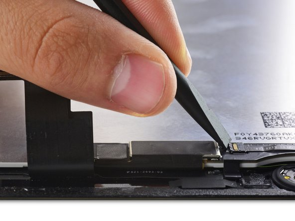 Use the flat end of a spudger to flip up the retaining flap on the Home Button cable socket.