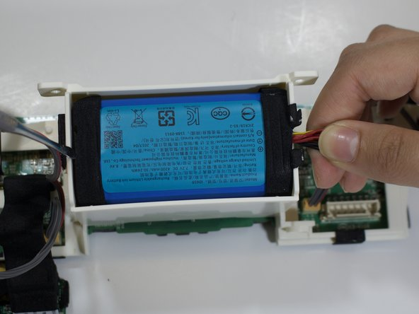 Insert the spudger along the battery edge and firmly hold the wires. Lift both sides up. The battery will pop out from its encasement.