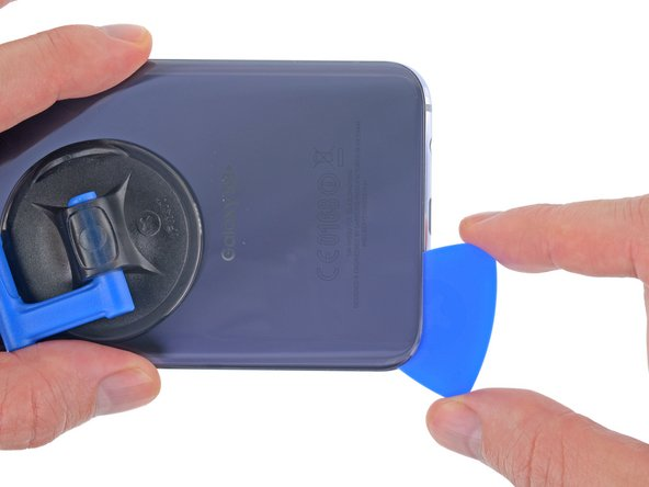 Continue slicing through the adhesive along the bottom edge of the phone.