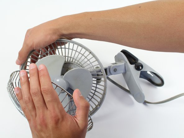 Now work your way around the edge of the fan cage and pull it away from the plastic body.