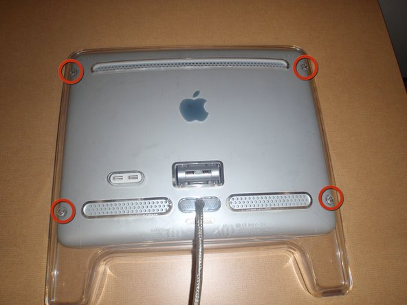 The USB ports are located on the back side of the monitor, below the plastic cover and metallic panel; on the lower left hand side.