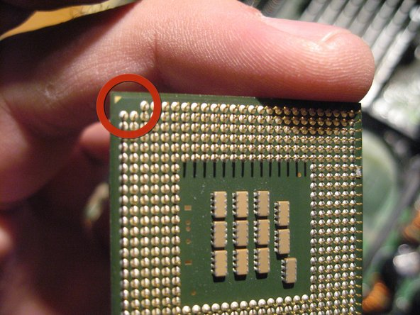 Take note of the one corner that has a few pins missing and a guide arrow.  This processor chip will fit into the PGA one way and this serves as a guide.