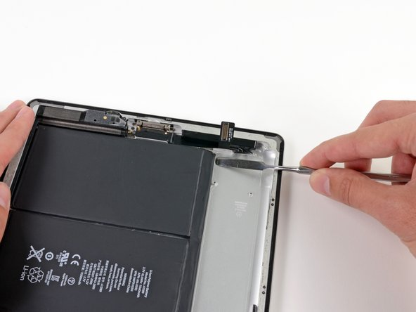 Insert the flat end of a metal spudger underneath the battery near the bottom of the iPad.