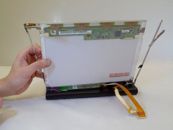 Using one hand, gently lift the LCD screen out of support arms.