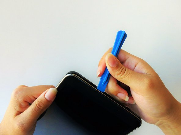 At the top of the tablet, nudge the blue plastic opening tool between the back plastic casing and the front panel's metal rim.