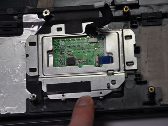 Slowly slide the frame in the direction of the keyboard hole on the plastic panel until the frame is released from the metal latches.