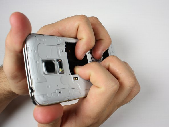 Image 1/3: Apply pressure to the battery slot on back of the phone to separate the midframes.