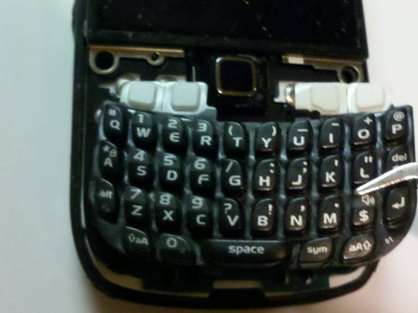 Image 2/3: Using tweezers, remove the keyboard buttons from the phone.