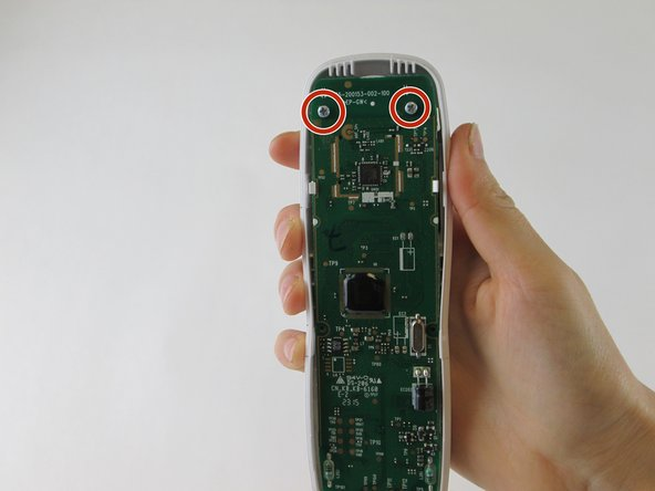 Using a screwdriver, remove the two 10.0mm Philips #0 round head screws at the top corners of the handset motherboard.