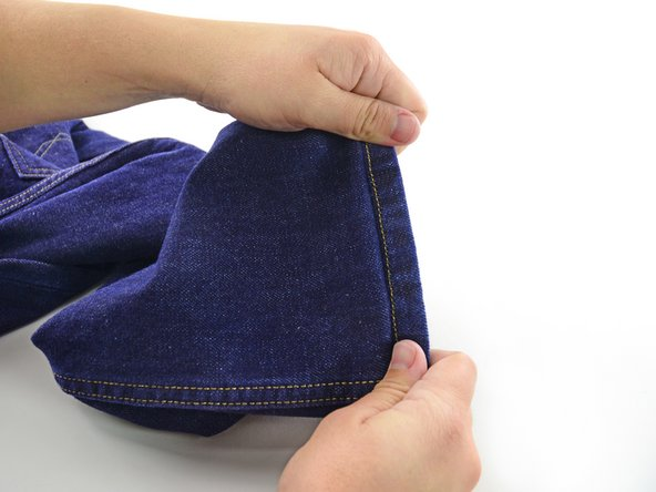 Image 2/2: Clip the threads that attach the jeans to the sewing machine.