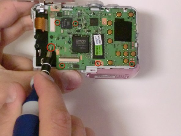 Using a #00 Philips screwdriver, unscrew the screws connecting the logic board to the camera.