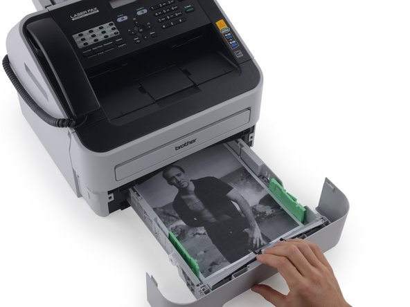 Continue pulling until the paper tray is free of the fax machine.