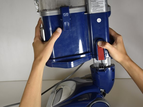 Lift this upper plastic body of the vacuum cleaner up with your hands while continuing to press on the circular region of the latch.