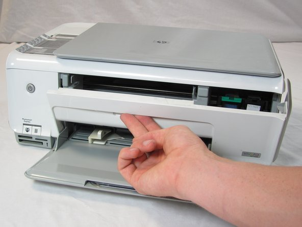 Image 2/2: Insert your fingers into the slot in the printer door and pull to rotate the gate down.