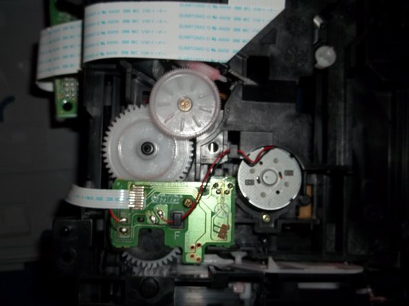 Turn disc drive over so you can see the gears on the bottom.
