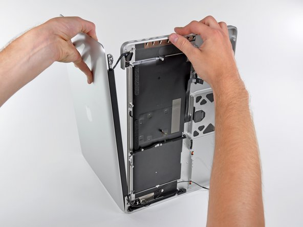Lift the display up and away from the upper case, minding any brackets or cables that may get caught.