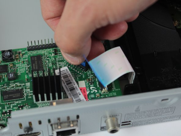firmly grip the hard plastic tab attached to the base and pull upwards. It is important no to tear the ribbon cables.