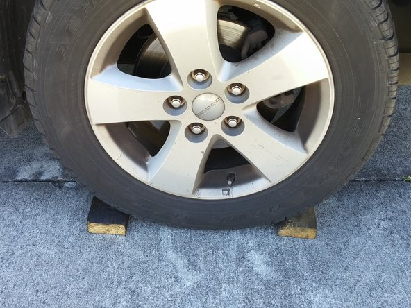 Chock (forcefully wedge an object, such as a wood block, between tire and pavement) the wheel on the opposite corner of the wheel you are working on, so that the vehicle cannot roll forward or backward.
