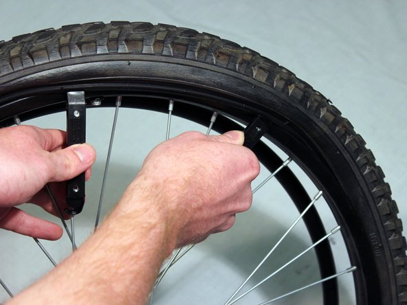 Holding one tire lever in place, slide the other lever around the rest of the wheel until the side of the tire is completely free of the rim.