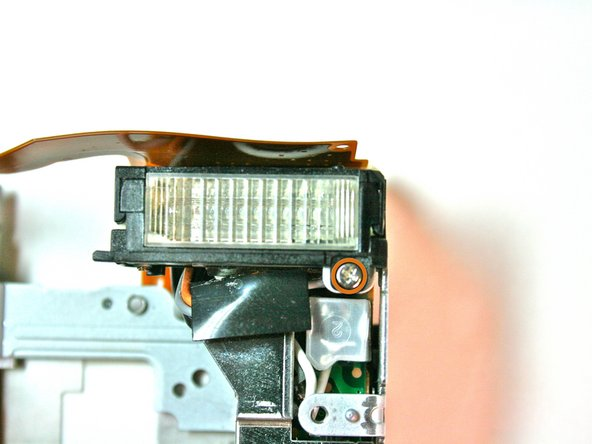 Remove the 3.3 mm screw from underneath the clear plastic flash unit on the front side.
